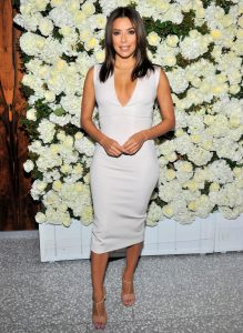 "Eva Longoria is 5'2"". She's wearing a plunging v neck dress, and t-strap shoes. Both are considered elongating for petites."